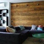 гостиная, угловой диван, зеленый круглый журнальный столик, стена из досок в комнате, диванные подушки с геометрическими узорами