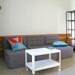 место отдыха, прямые линии в дизайне комнаты, сдержанная цветовая гамма, металлический стеллаж, сочетание материалов в интерьере, журнальный стол на колесиках, модульный диван, лаконичный торшер, дерево в интерьере
