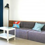 место отдыха, прямые линии в дизайне комнаты, сдержанная цветовая гамма, сочетание материалов в интерьере, журнальный стол на колесиках, модульный диван, лаконичный торшер, дерево в интерьере, насыщенный синий акцент