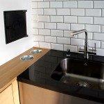 детали интерьера, кухня, мойка, белая плитка с темной затиркой, черная столешница, печная дверца в интерьере кухни, подстаканники под моющие средства кухне